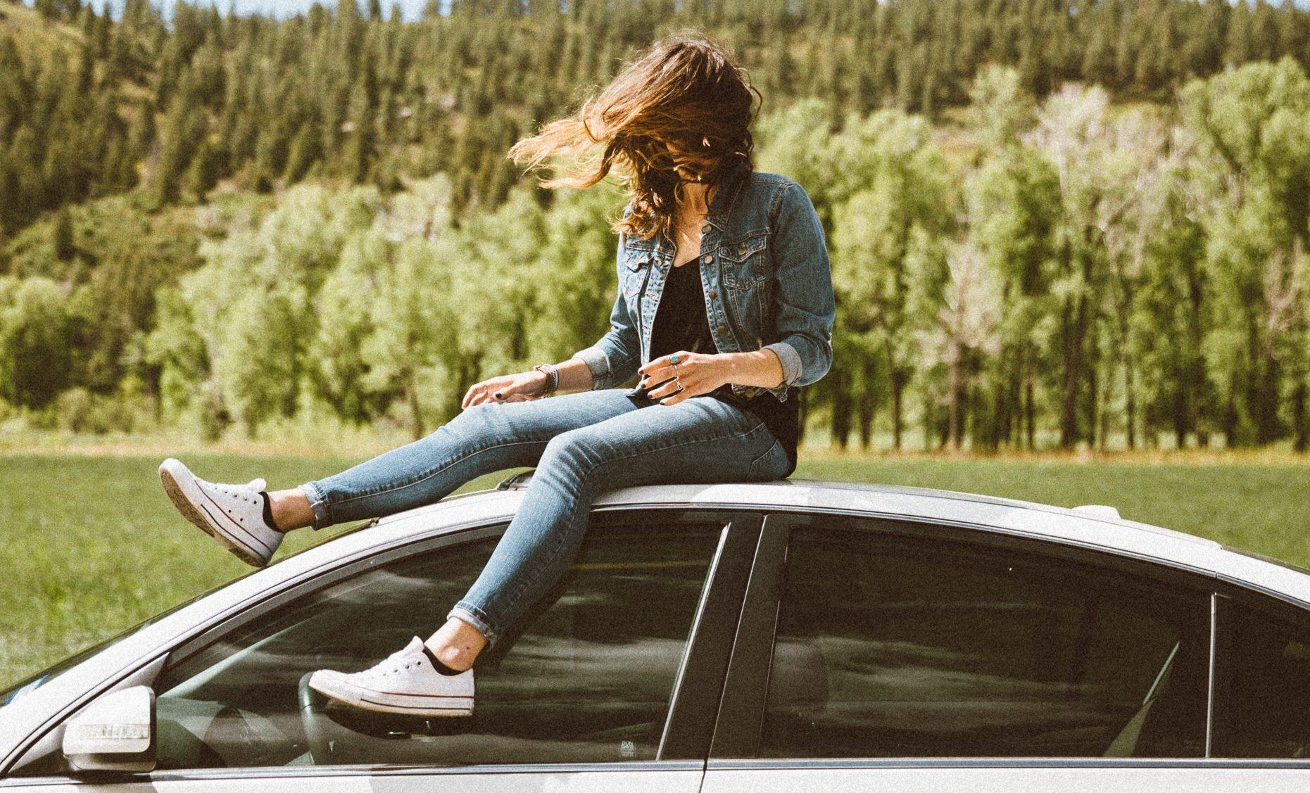 Junges Mädchen sitzt auf dem Autodach.